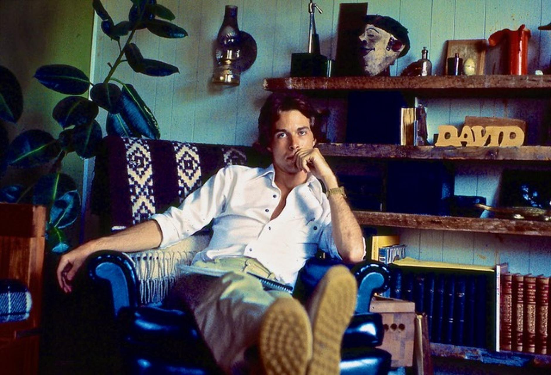 David when he was younger, relaxing in a living room.