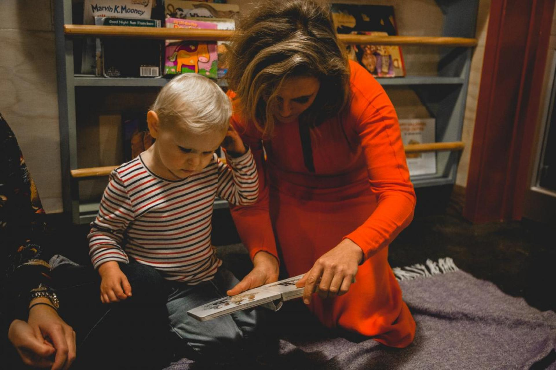 Photograph of Tift Merritt wearing a red dress, reading a book to her young daughter.