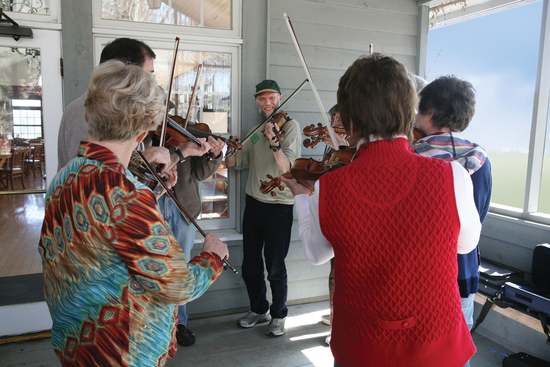 A group of fiddlers participating in an outdoor class