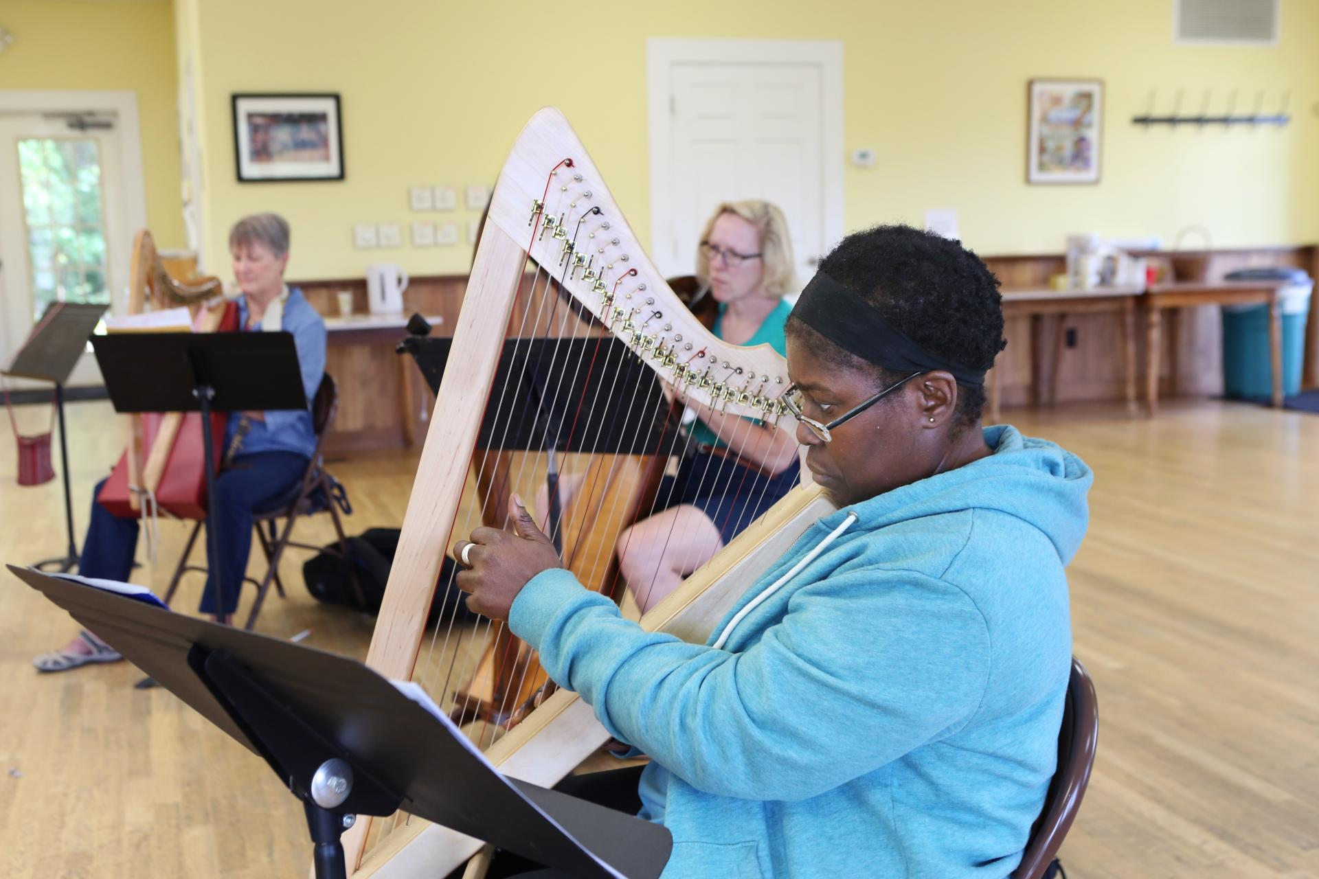 A John C Campbell Folk School student playing harp in a