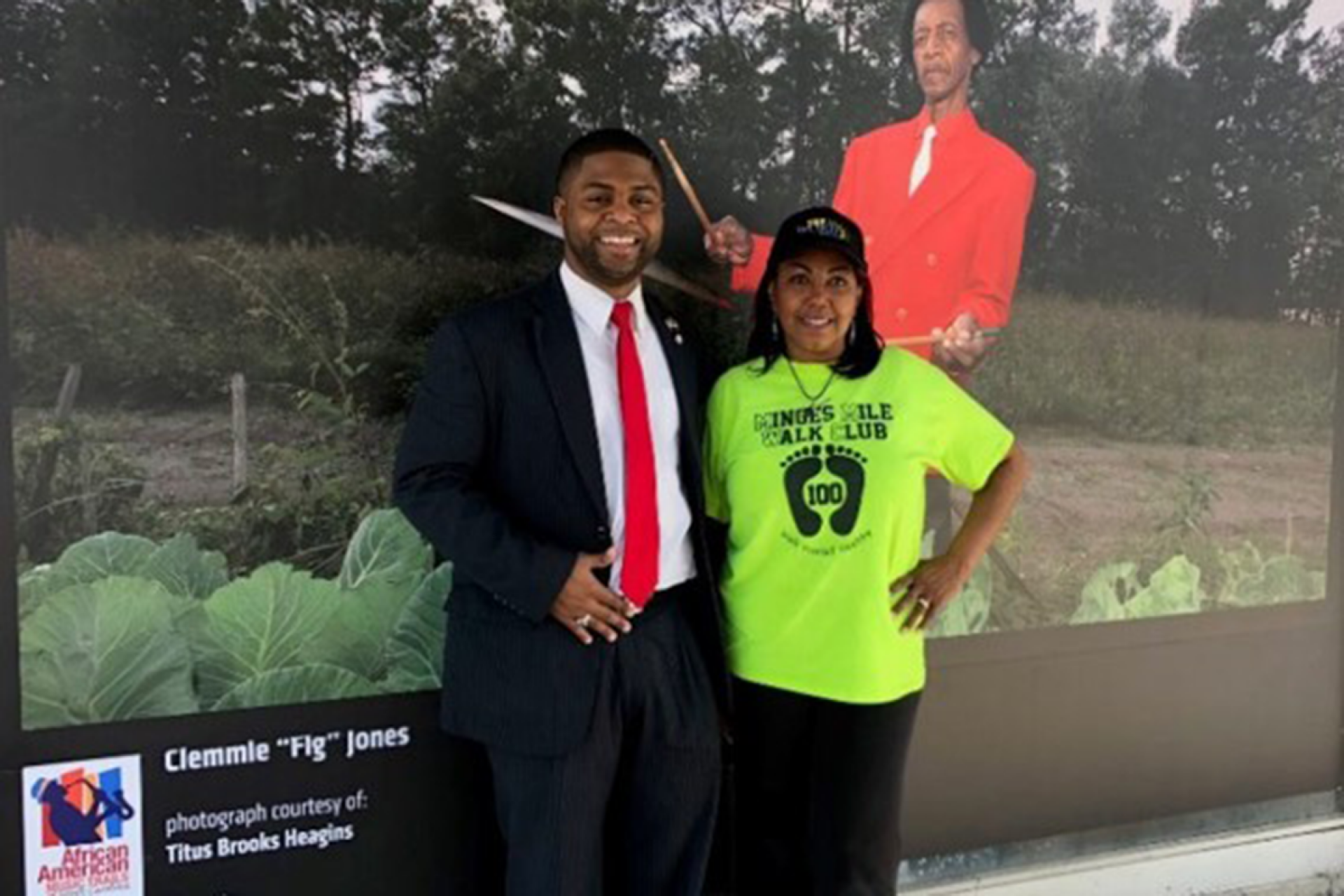 "City of Kinston Mayor Don Hardy and artist Lessette Korenegay in front of a portrait of Clemmie ""Fig"" Jones"