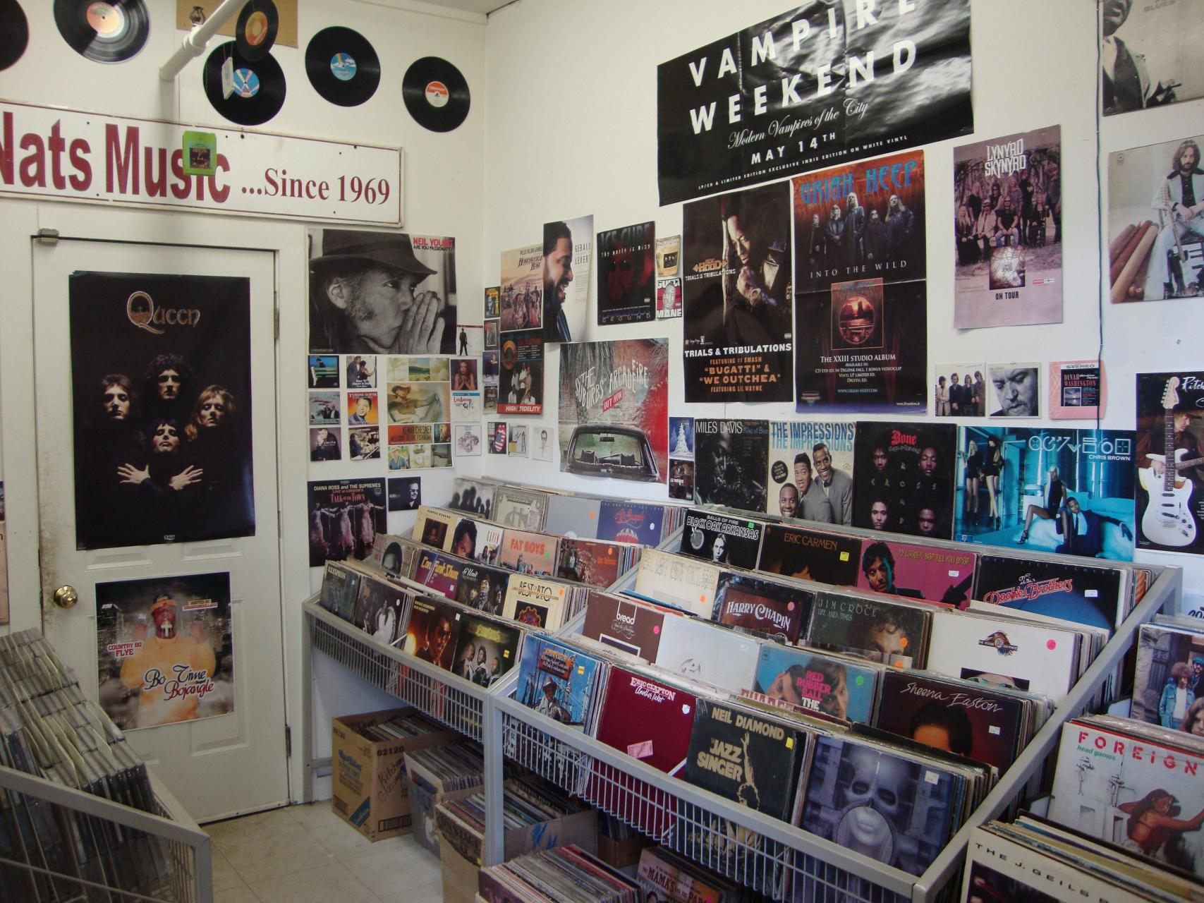 An interior shot of Nit Nats, with records, posters, and a sign from their original location on display