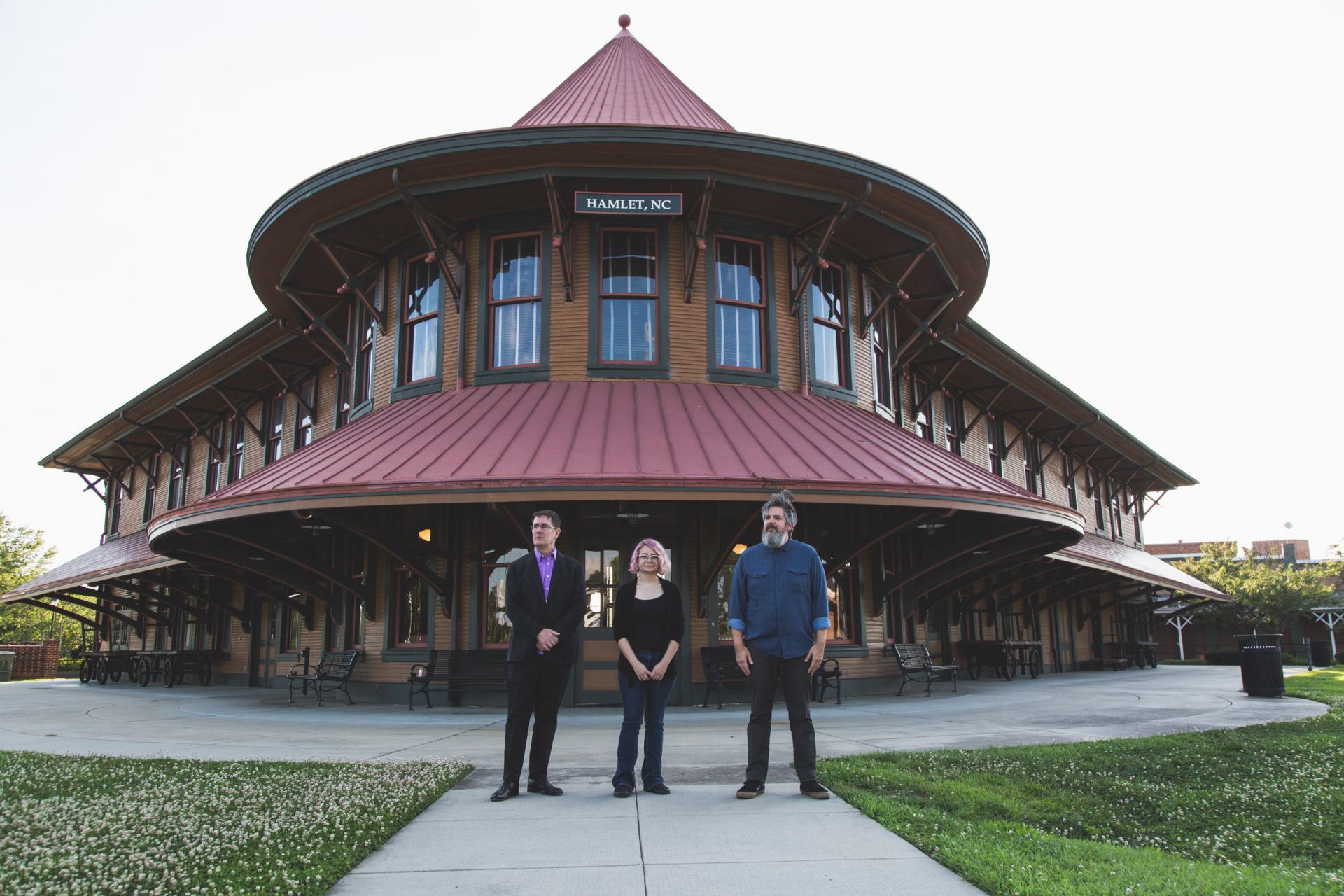 John Darnielle, Jamie Staton, Matt Douglas stand outside the Hamlet Depot & Museum