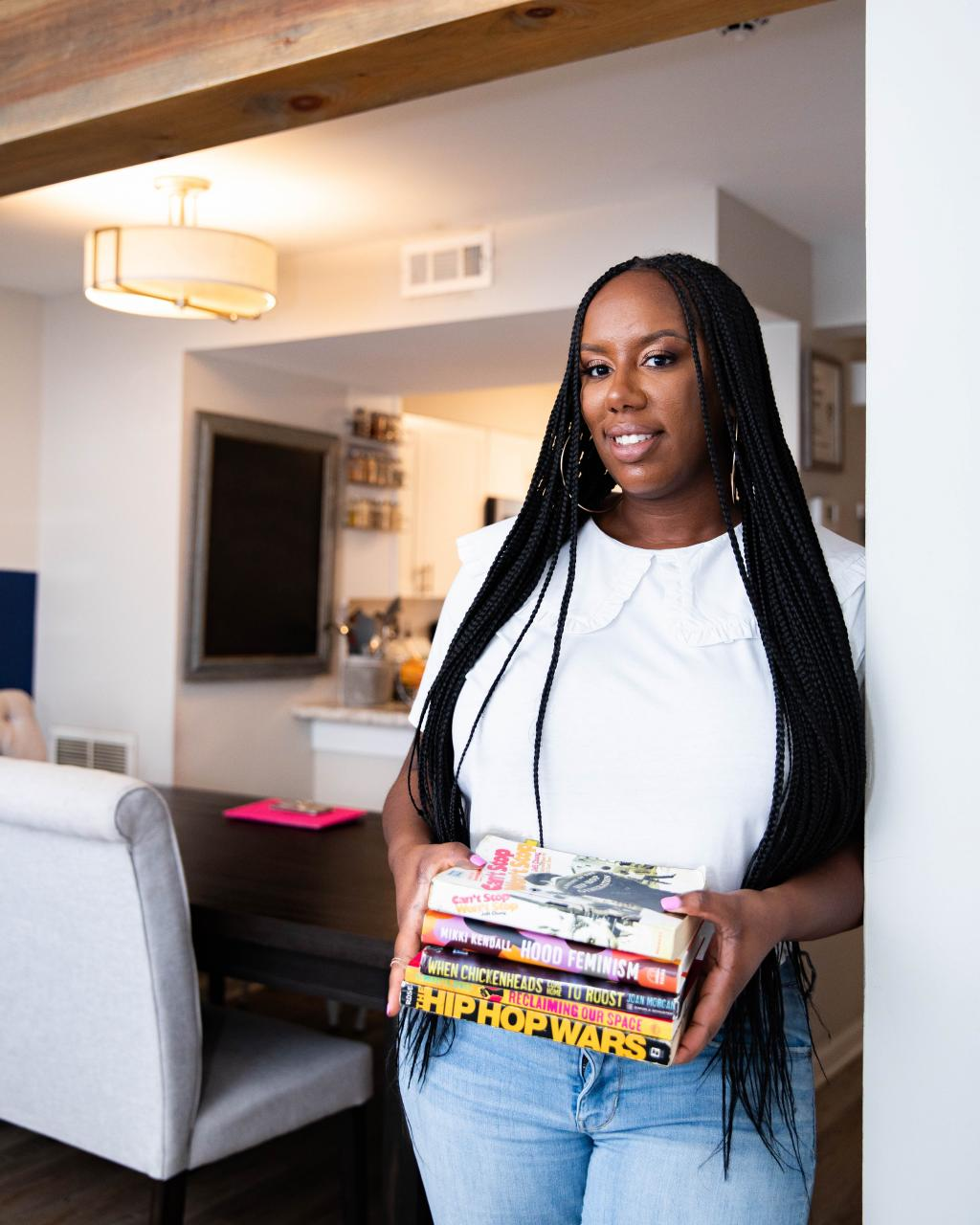 Photograph of Kyesha Jennings, a smiling Black woman holding a stack of books about Hip-Hop