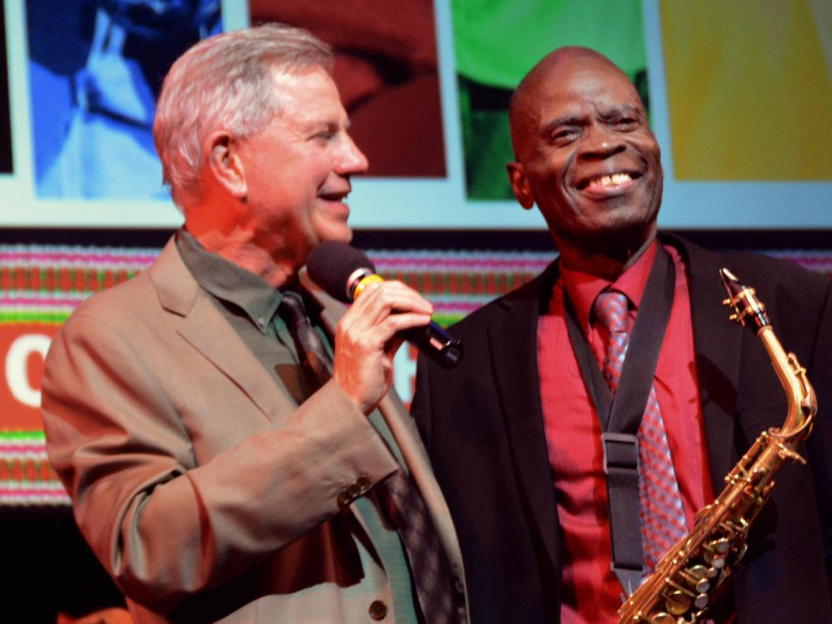 Wayne Martin and Maceo Parker arm in arm on stage. Wayne holding a microphone, Maceo with a saxophone