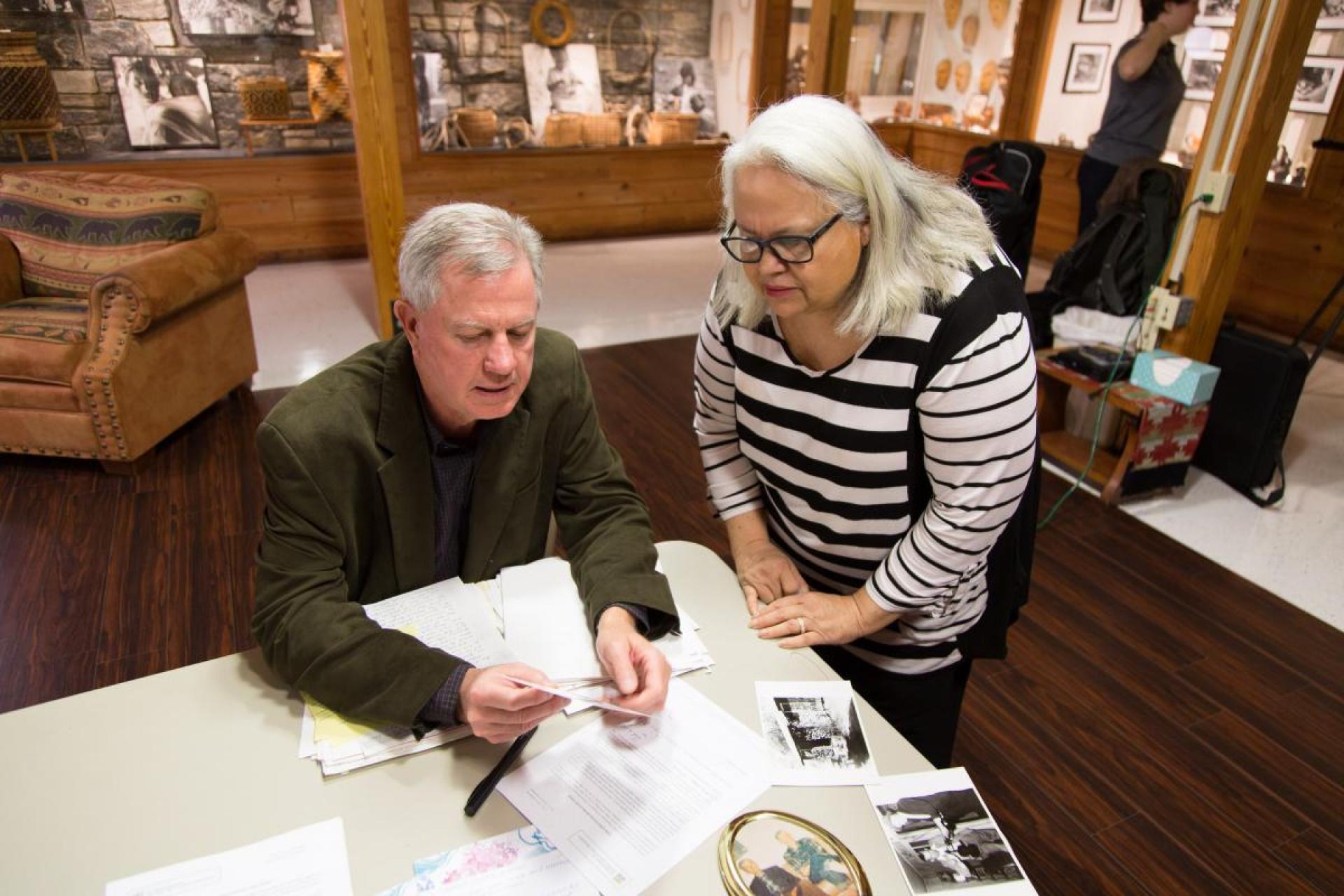 Wayne Martin and a member of the Sneed family looking at photographs at a table