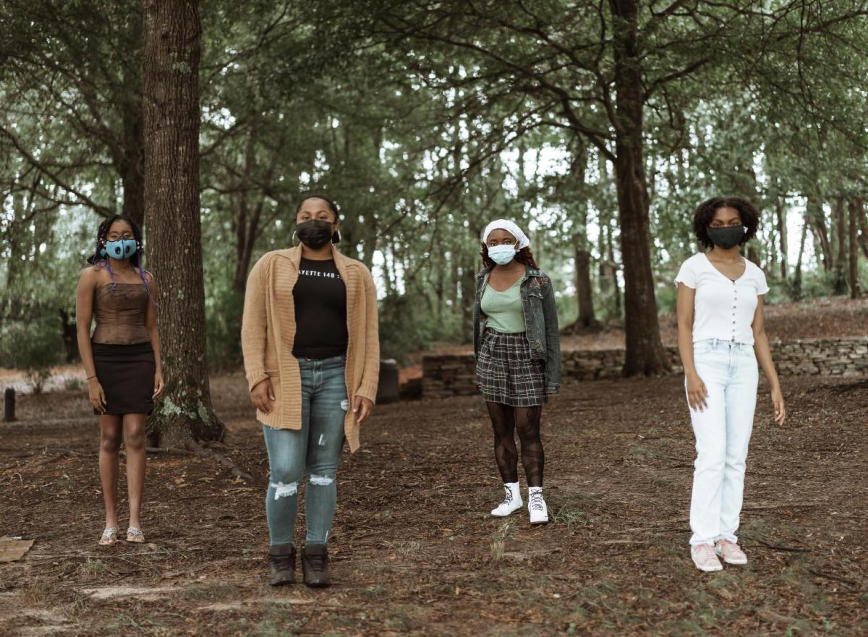 A group of 4 girls in the woods wearing facemasks