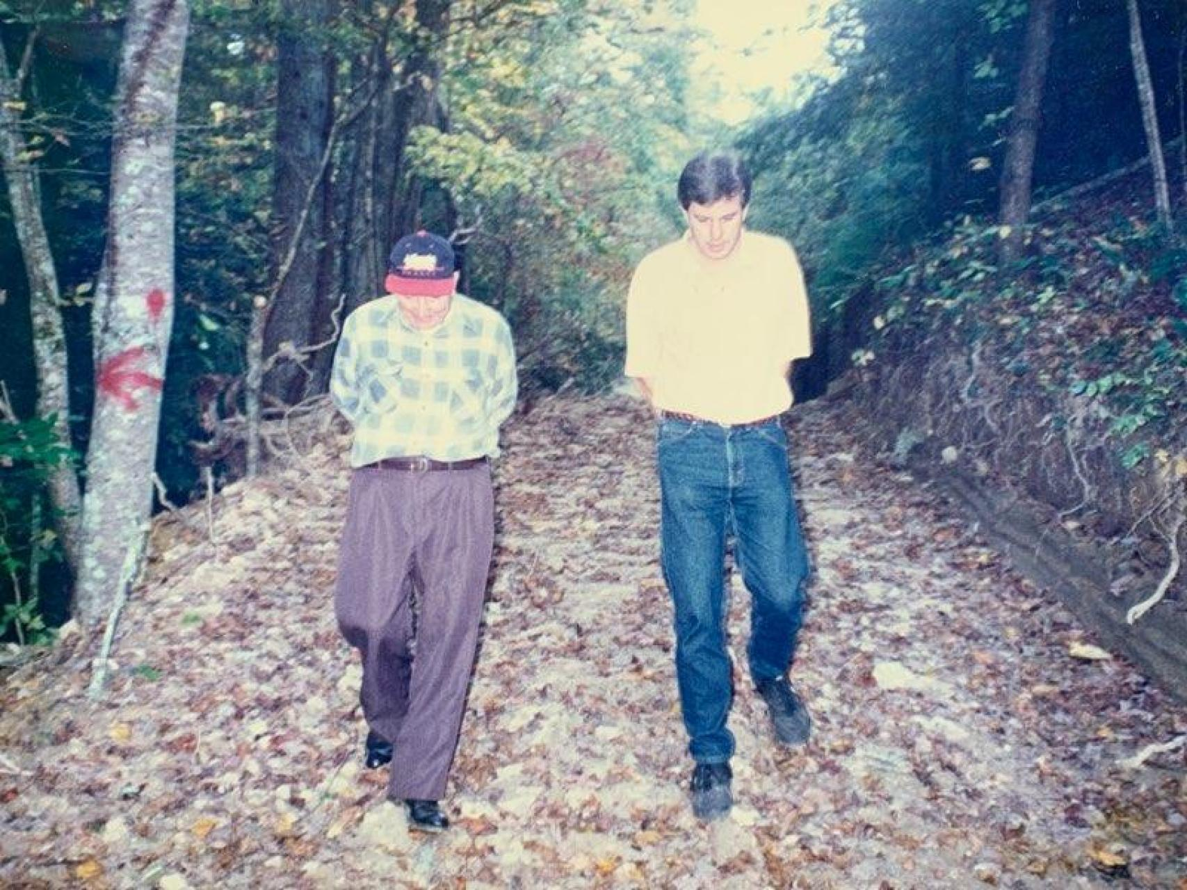 Wayne Martin and Doug Wallin walking on a wooded path