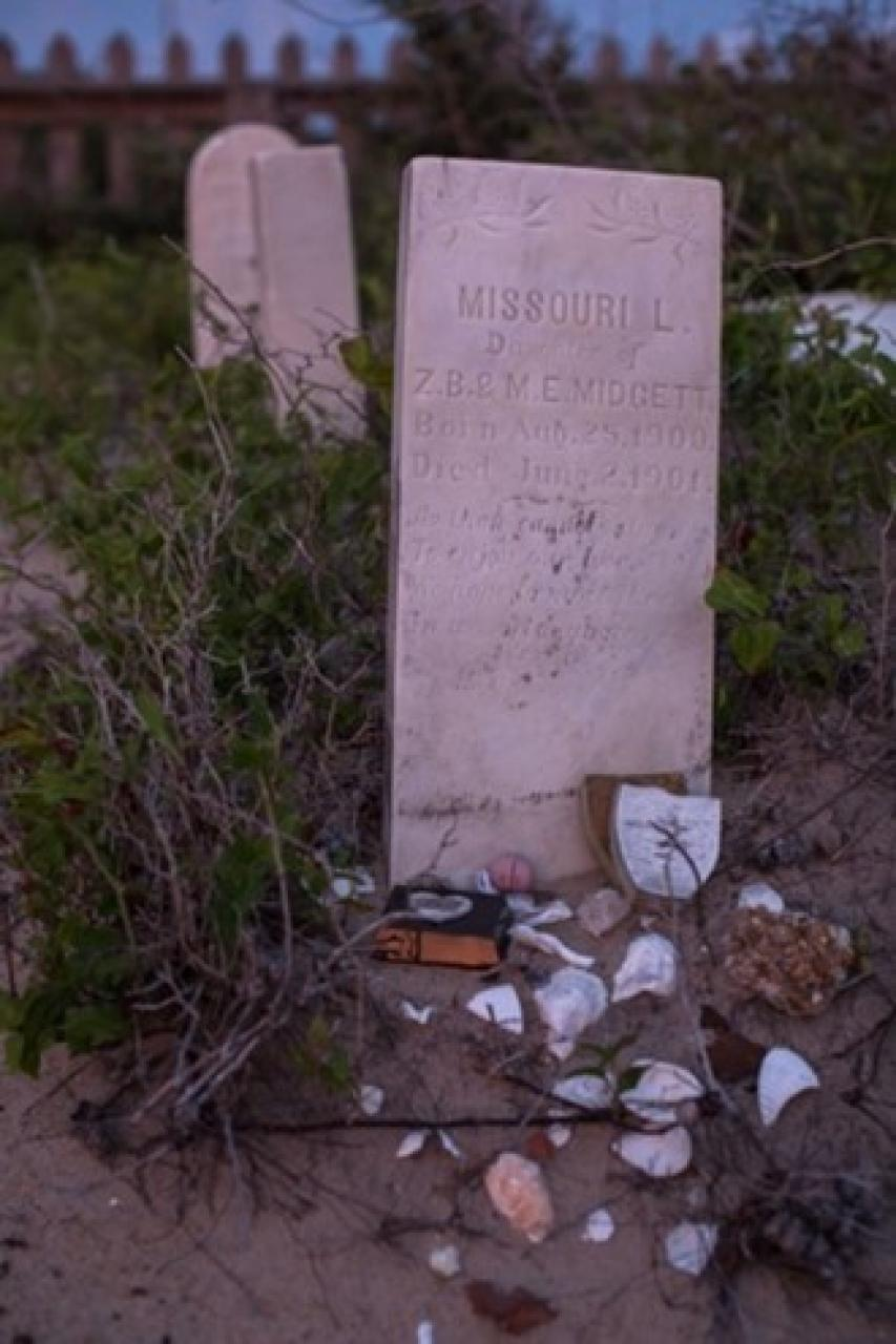Seashells and memorabilia adorn an old headstone at the Salvo Community Cemetery.