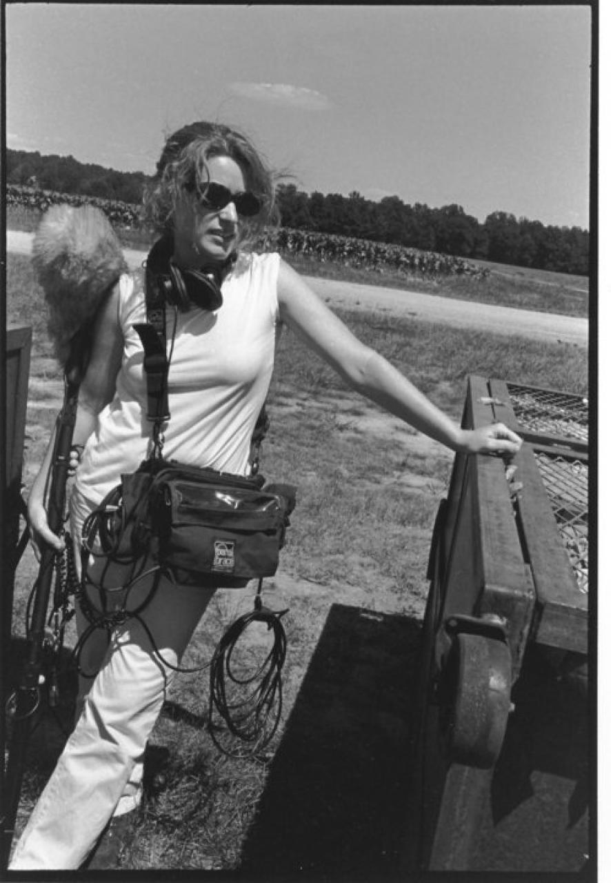 B&W photo of a woman in a field with camera equipment.