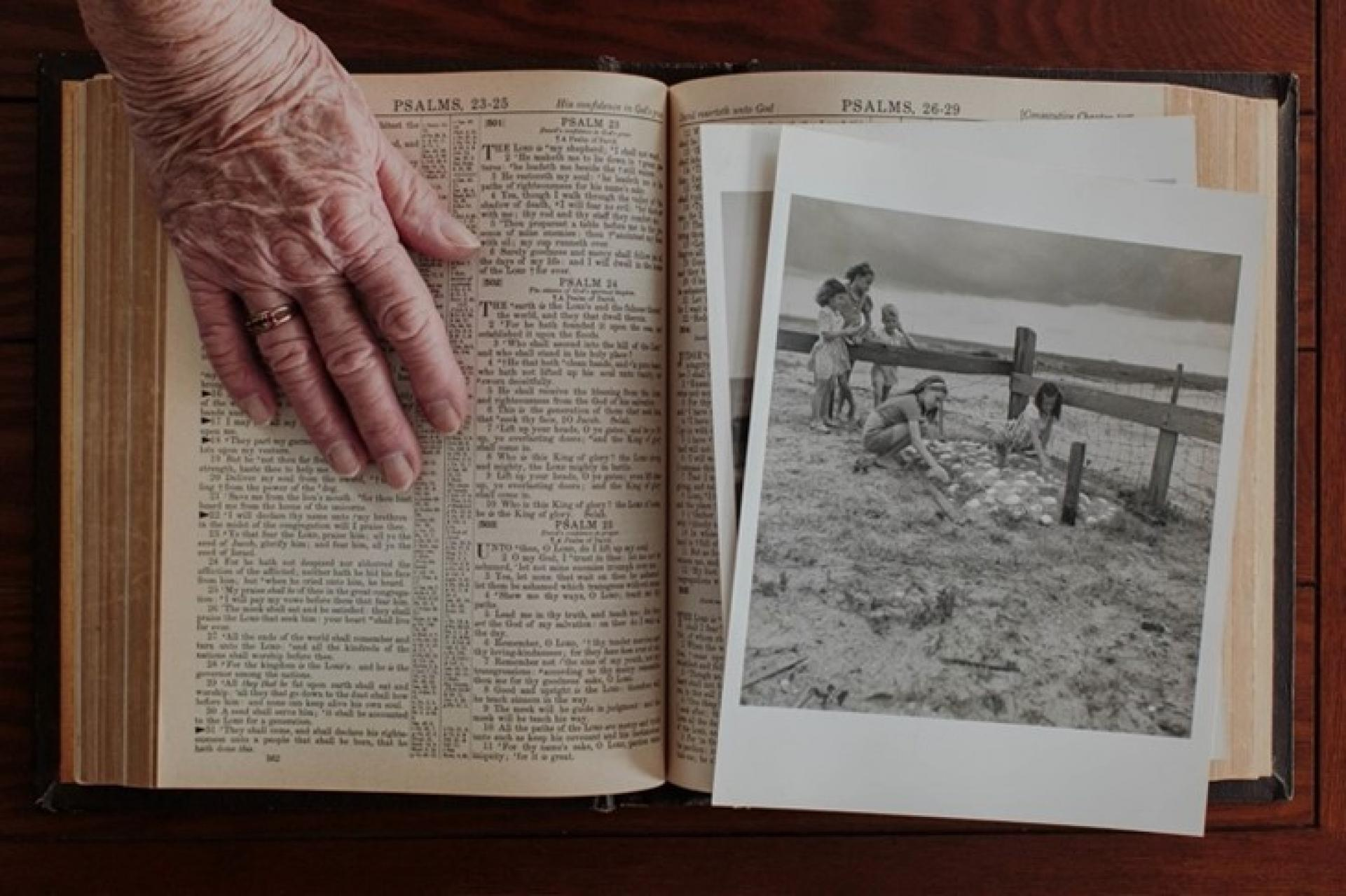 Jean Hooper's hand rests on top of the family bible, next to an archival image of her playing in the community cemetery as a child.