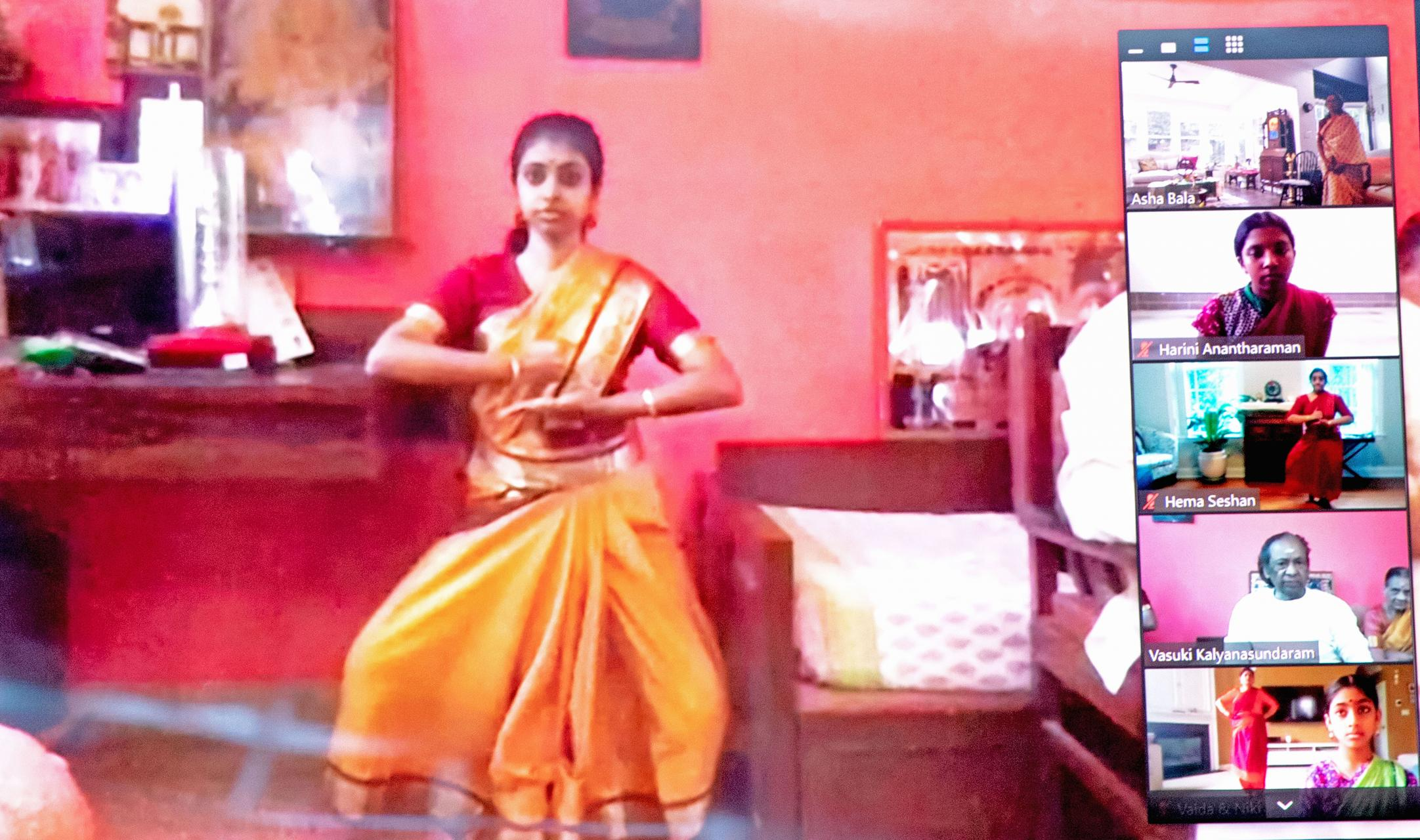 Screenshot of a virtual dance class. A young woman in a sari is captured mid dance move. Five video boxes of participants are on the right side of the screen.