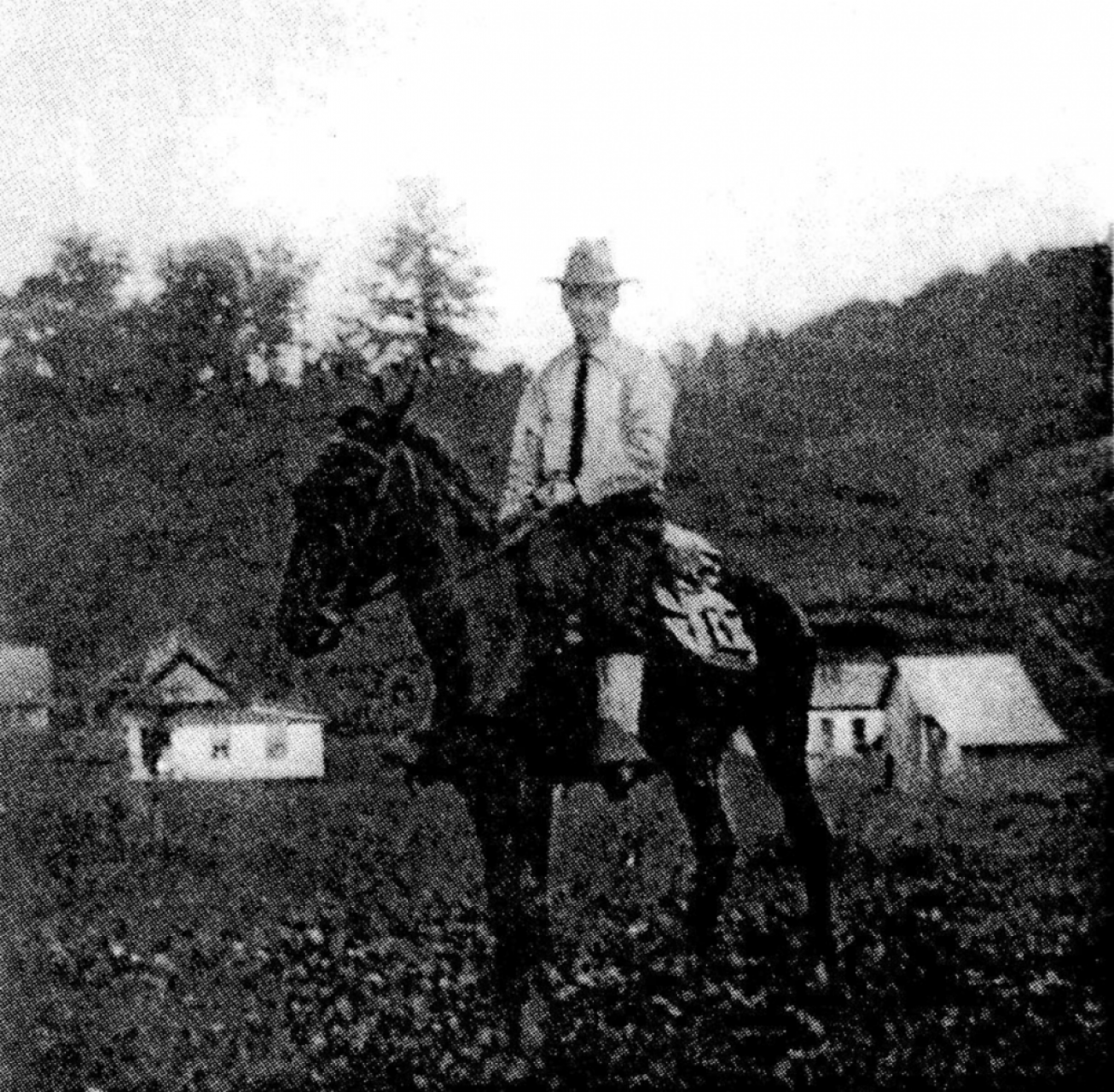 A black and white photo of a man on a horse.