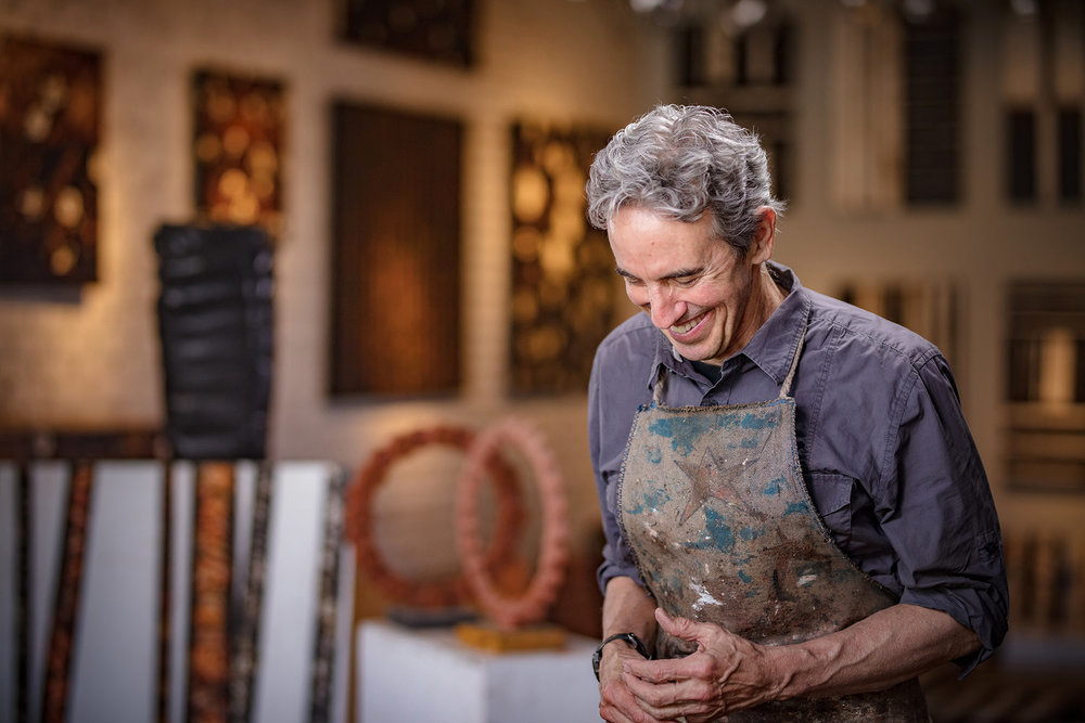 Artist looking down, smiling, wearing apron, in art studio