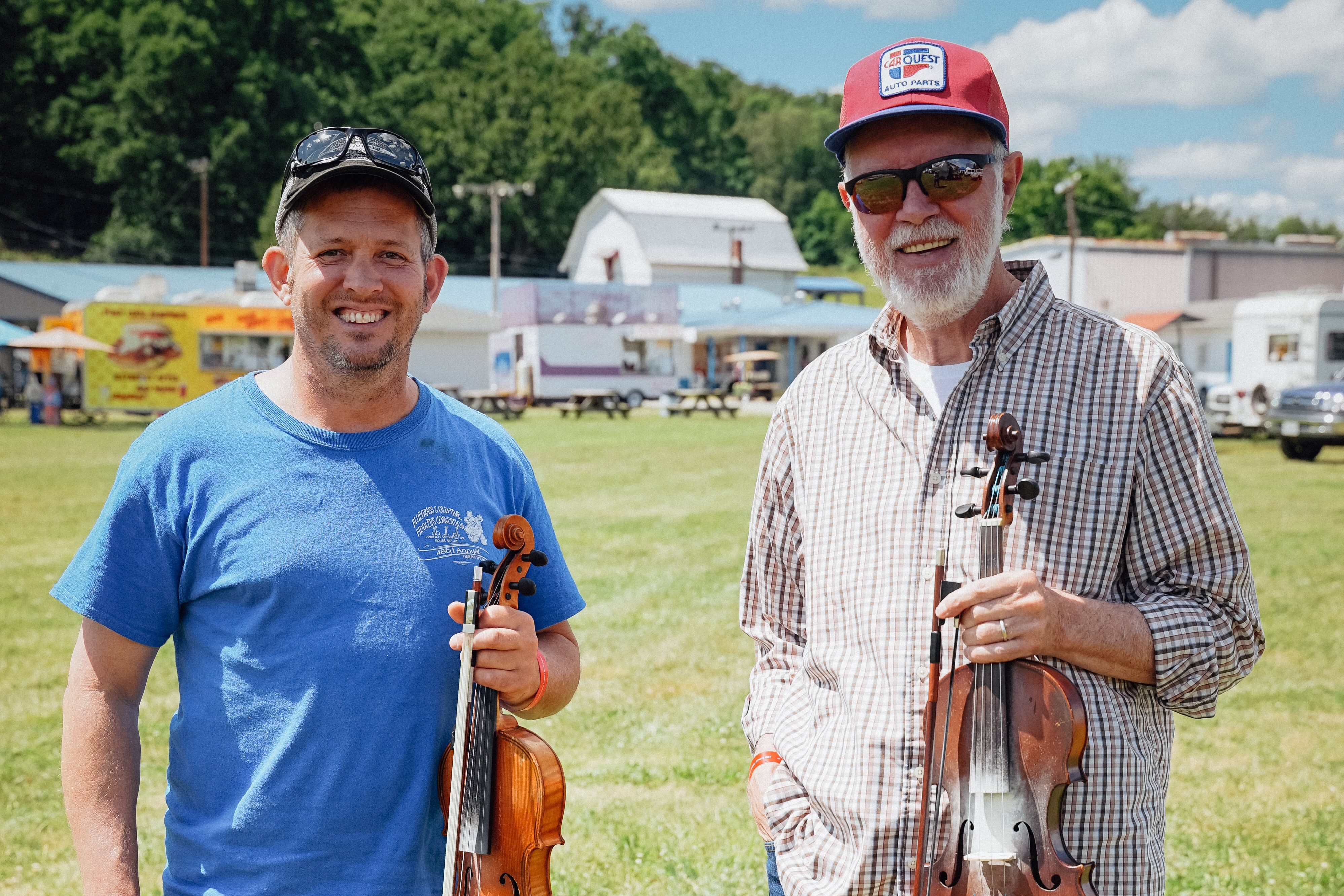 Chad Ritchie, a white man holding a fiddle, stands in on a lawn next to Richard Bowman, an older white man also handing a fiddle.