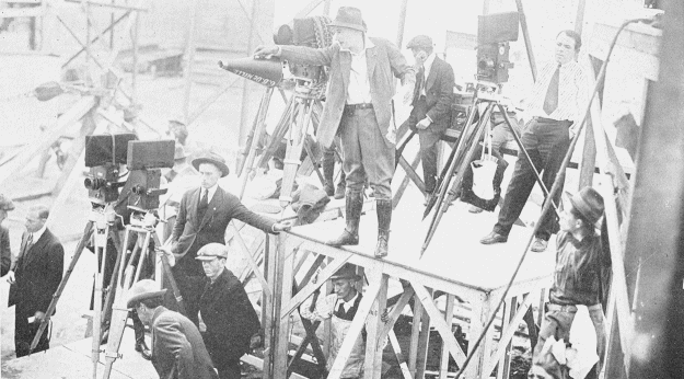 DeMille (center) directing a film. Image from the New York Institute of Photography.