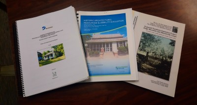 Three spiral bound architectural survey reports spread out on a table.