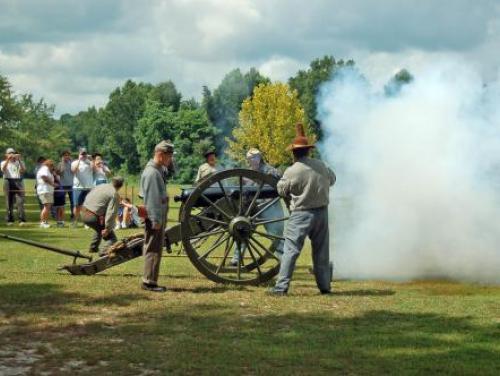 Visitors watch a cannon blast at Bentonville Battlefield
