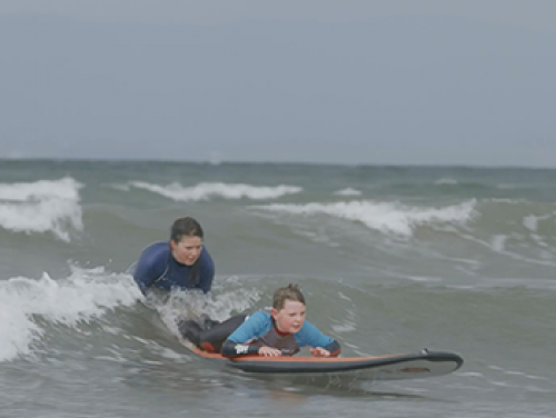 Two boys in the ocean, one on a surfboard