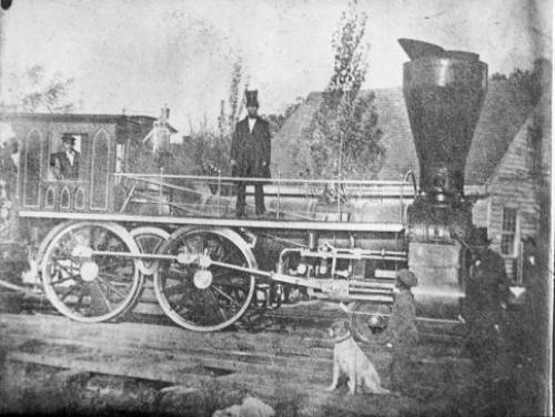 A Man Stands on a Raleigh and Gaston Railroad Locomotive