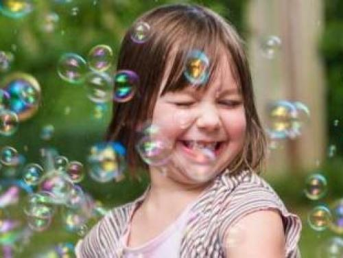 young girl with bubbles outside