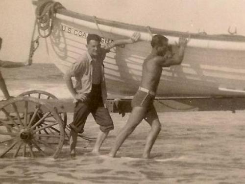 Three men push a boat to sea