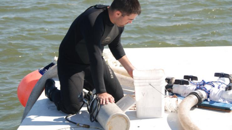 An archaeologist preps the drill used for in situ monitoring