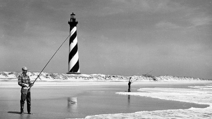 Surf fishing in the shadow of the Cape Hatteras Lighthouse, circa 1956.