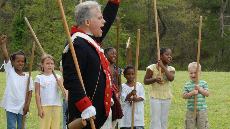 A Revolutionary War re-enactor cheers with kids