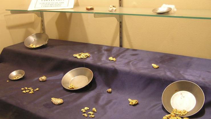 A display of gold pans and gold nuggets at Reed Gold Mine