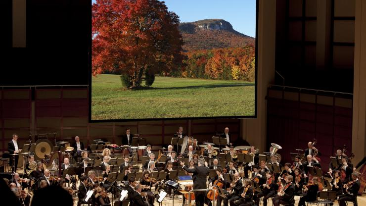 The North Carolina Symphony performs with an image of nature in the background