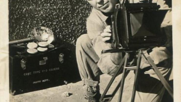 Photograph of Charles M. Allen Jr. of Mount Gilead, N.C., kneeling down looking over his Graflex Speed Graphic, Ground Camera Type C-3, mounted on a tripod, with the camera case and flash pictured on the ground in the background. Allen was serving in the U.S. Army Air Forces at Lowry Field in Denver, Colorado, in 1942 during World War II.