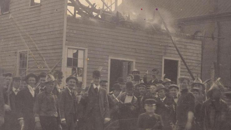 A mob stands at the ruins of Alex Manly's Daily Record office, destroyed November 10, 1898.