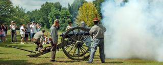 A crowd watches a cannon blast off at Bentonville Battlefield