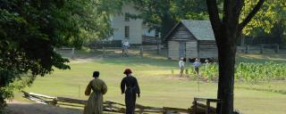 Interpreters Walk Along a Dirt Road at Durham's Duke Homestead