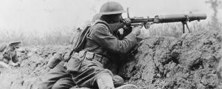 Two World War I machine gunners fire over a trench wall