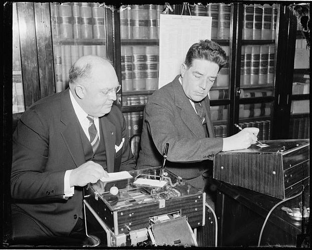 Warren learns how to use an electronic signature machine in 1938. Image from the Library of Congress.