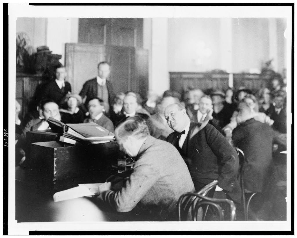Gaston Means in court. Means is in the center of the photograph with his head tilted toward the camera. Image from the Library of Congress.