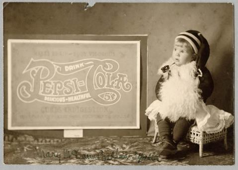 Caleb Bradham's daughter, Mary, poses with an early Pepsi poster, circa 1905-1910. Image from the N.C. Museum of History.