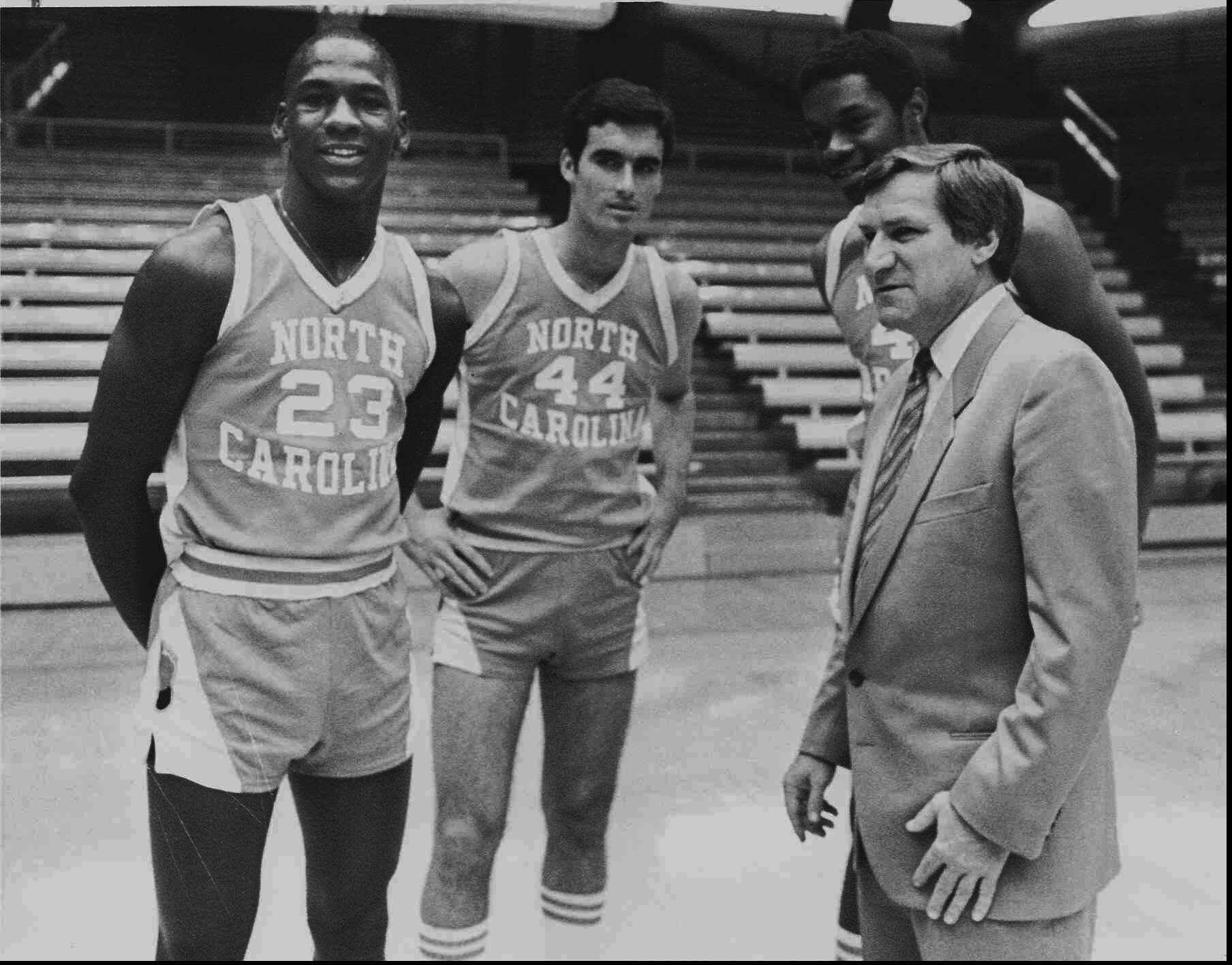 Dean Smith (left) with then-freshman Michael Jordan (far right), Matt Doherty and Sam Perkins of the 1982 UNC basketball team.