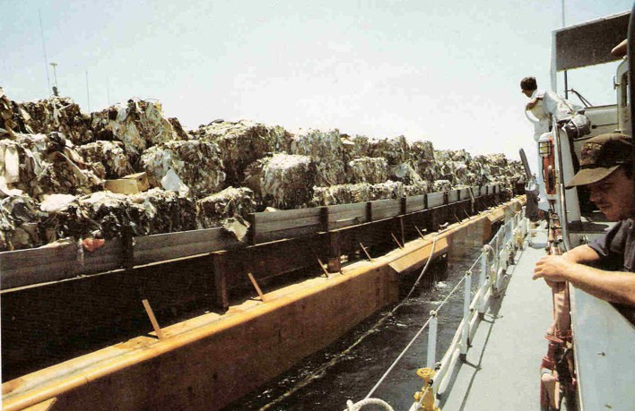 State and federal environmental officials examine the garbage aboard the Mobro 4000. Image from Vice.
