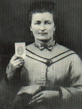 Malinda Blalock holding a portrait of her husband. Image from the Avery Museum.