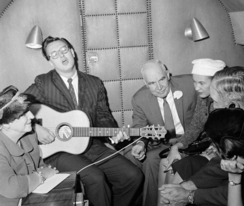 Loudermilk (second from the left) plays guitar aboard an airplane for Luther Hodges (third from the left) and others. Image from UNC-Chapel Hill Libraries.