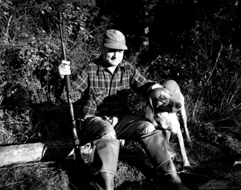 A man and Plott hound on a bear hunt in western North Carolina. Image from the State Archives.