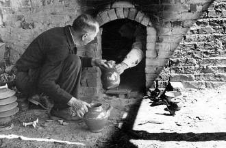 Two men unloading fired pottery from a kiln at Jugtown in 1938. Image from the State Archives