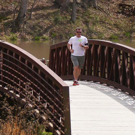 A jogger crosses a wooden bridge at William B. Umstead State Park in North Raleigh, North Carolina