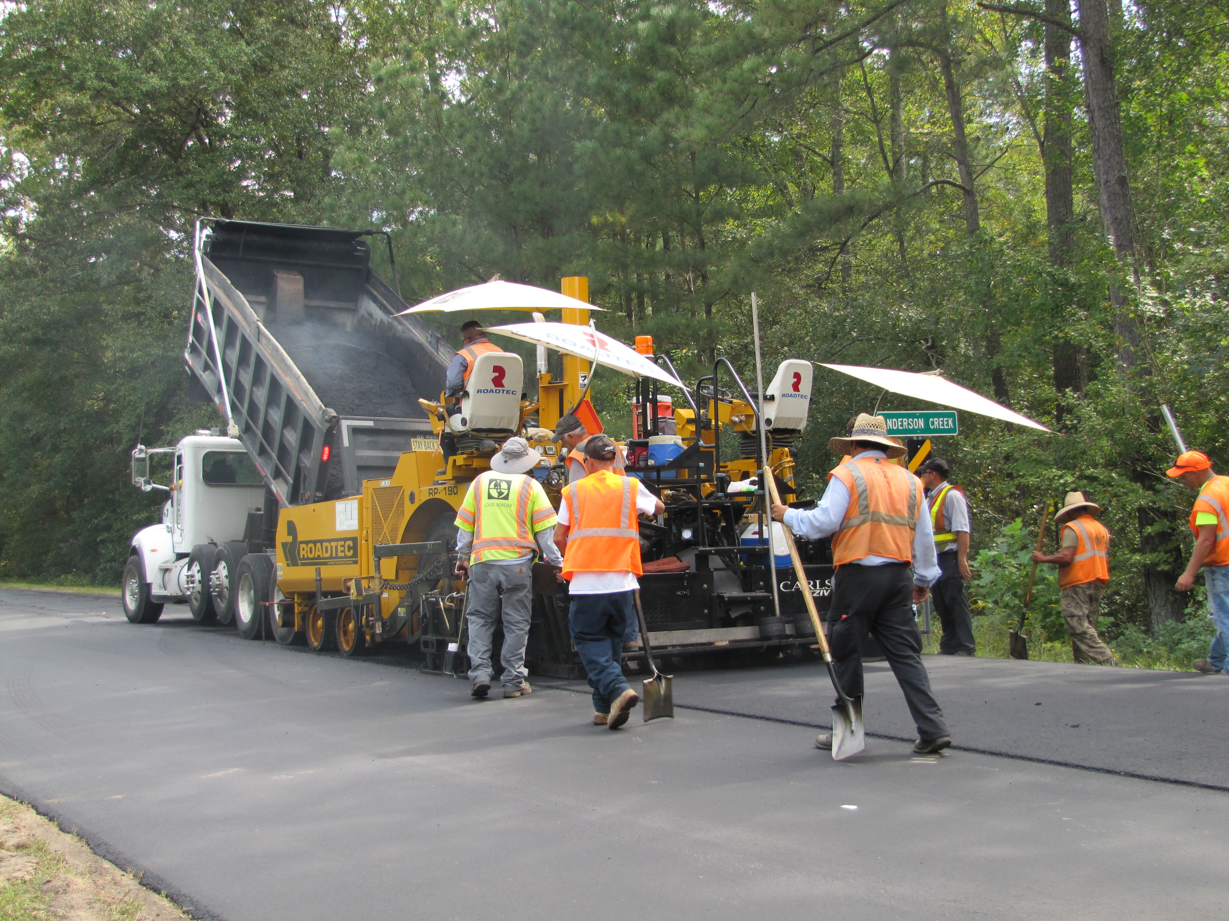 Truck and Construction Workers Paving A Road