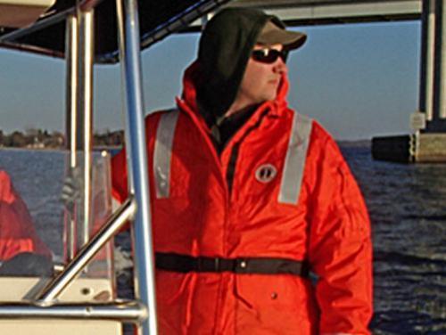 Man on boat in orange jacket