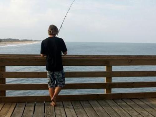 Man fishing on wooden pier