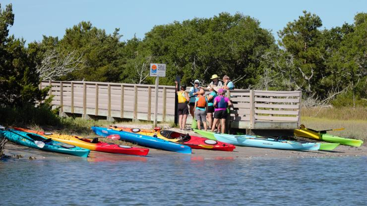 People stand on the end of a boardwalk next to kayaks along the shoreline.